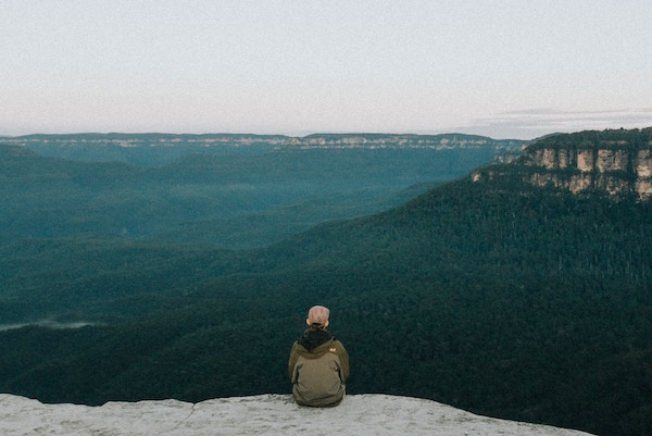 Man sitting and relaxing, looking over the Blue Mountains in NSW